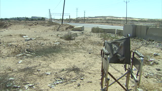 stockvideo's en b-roll-footage met exterior shots of the no man's land just inside gaza at the erez crossing with goats grazing amongst scrubland and a damaged abandoned wheelchair by... - israëlisch leger