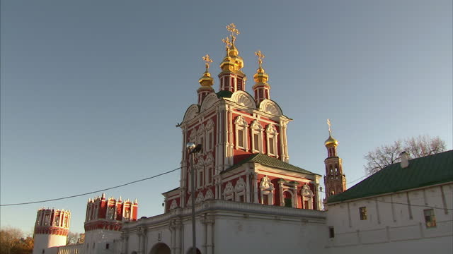 exterior shots of the novodevichy convent including shots of its gilded domes and towers against a clear blue sky and locals walking in a nearby park... - gilded stock videos & royalty-free footage