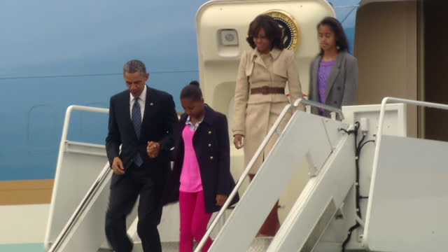 exterior shots of the obama family getting off the plane in northern ireland barack michelle their children malia sasha walking down steps to greet... - バラク・オバマ点の映像素材/bロール