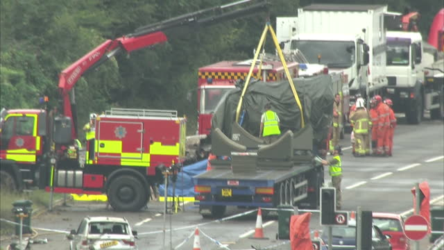 exterior shots of the operation to recover the crashed hawker hunter jet from the a27 with a crane moving it into position over a flatbed truck on... - ショーハム・バイ・シー点の映像素材/bロール