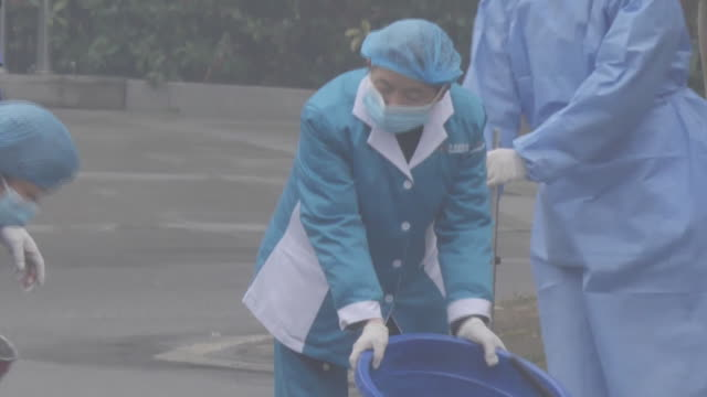 exterior shots of the outside of a hospital and shots of medical staff wearing protective clothing including gloves face mask and hats and cleaning... - wuhan stock-videos und b-roll-filmmaterial