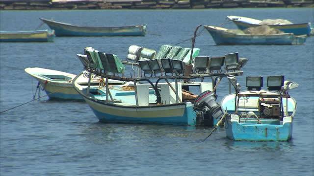 vídeos de stock, filmes e b-roll de exterior shots of the palestinian turkish flags fying side by side at the port of gaza and empty fishermen boats anchored in the harbour on july 29... - ancorado