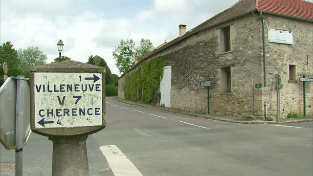 Exterior shots of the picturesque commune of VillersenArthies in Vald'Oise with a few cars passing traditional rustic buildings and a road leading...