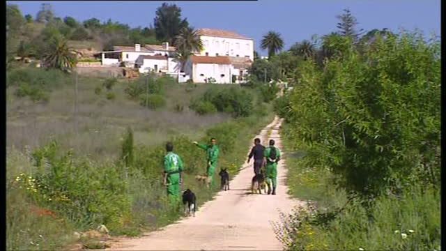 exterior shots of the police station, police officers and police officer with a sniffer dog scouring nearby overgrown area on may 8, 2007 in praia da... - kate mccann stock-videos und b-roll-filmmaterial