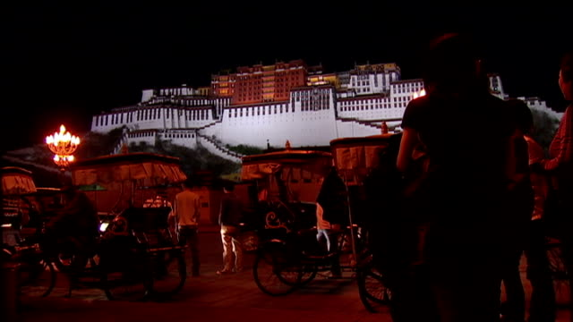 vídeos de stock, filmes e b-roll de exterior shots of the potala palace in lhasa tibet at night time illuminated with tourists in the square in front of it taking photos rickshaw... - autoimolação