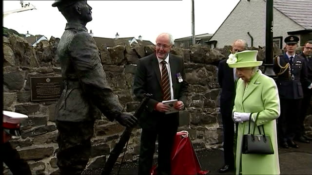 exterior shots of the queen and prince philip unveiling a statue and plaque commemorating robert quigg a local soldier from bushmills who was awarded... - the victoria cross stock-videos und b-roll-filmmaterial