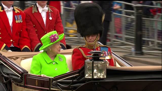 exterior shots of the queen and prince philip waving from a horse-drawn carriage during a procession from buckingham palace to horseguards parade for... - 軍旗分列行進式点の映像素材/bロール