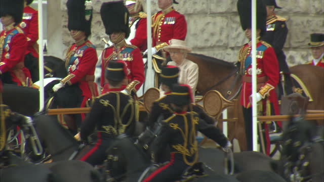 Exterior shots of the Queen and Royal party looking on as members of the King's Troop Royal Horse Artillery Life Guards and the Blues and Royals ride...