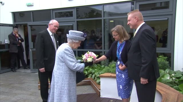 vídeos de stock, filmes e b-roll de exterior shots of the queen being presented with a posey of flowers before unveiling a plaque to commemorate the official opening of the robertson... - 2017