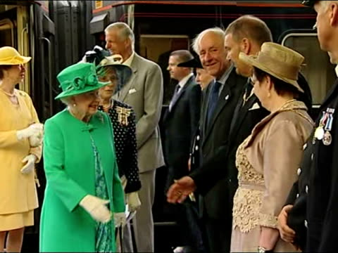 Exterior shots of the Queen dressed in emerald green arriving in Kendal greeting and shaking hands with officials in line on the train platform Queen...