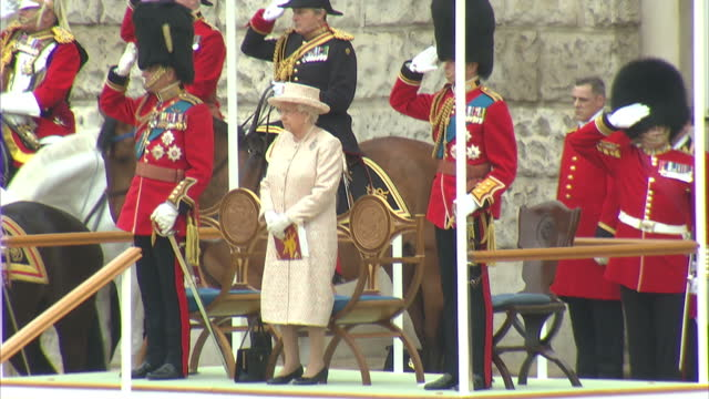 Exterior shots of the Queen Prince Philip and the Duke of Kent looking on and saluting as the Colour of the Welsh Guards is presented to Ensign by...