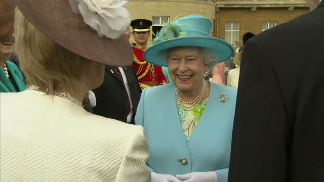 exterior shots of the queen speaking to invited guests in buckingham palace gardens after presenting the colours to the grenadier guards queen... - 近衛兵点の映像素材/bロール