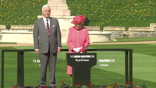 vídeos de stock, filmes e b-roll de exterior shots of the queen walking onto windsor castle grounds and pressing a red button to launch the 2018 london marathon on 22 april 2018 in... - 2018
