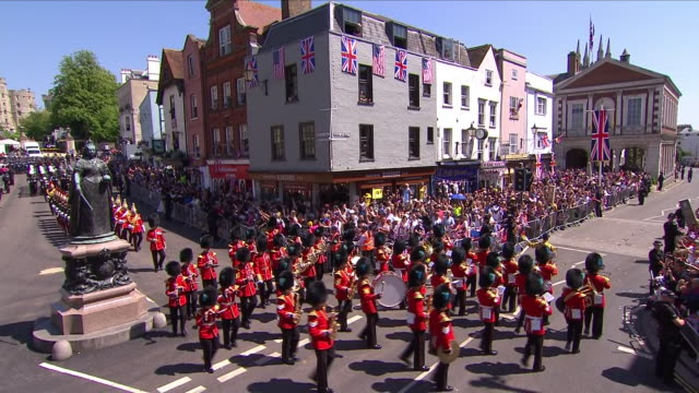 stockvideo's en b-roll-footage met exterior shots of the royal military parade procession departing from windsor castle and marching past the staue of queen victoria led by the band of... - britse leger