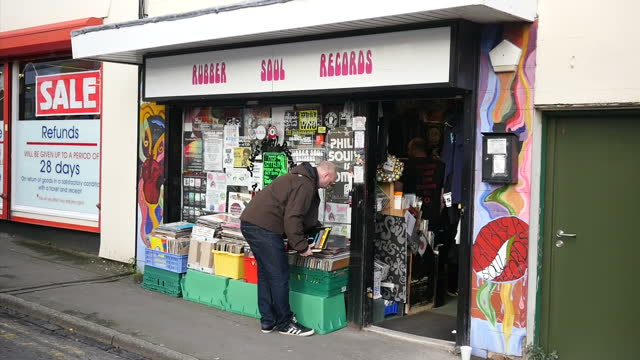 vídeos y material grabado en eventos de stock de exterior shots of the rubber sole record shop in stoke on trent with a man outside browsing through piles of vinyl lp records on december 29 2015 in... - tienda de discos