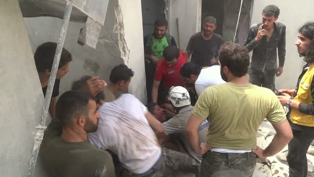 Exterior shots of the rubble and destruction in the immediate aftermath of an airstrike on Aleppo as a man carries the body of a young child WARNING...