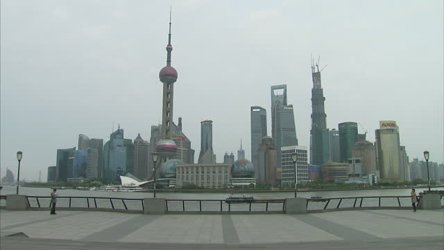 exterior shots of the shanghai city skyline and people walking along the embankment next to the huangpu river. shanghai city skyline, seen from the... - river huangpu stock videos & royalty-free footage