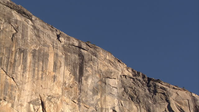 exterior shots of the sheer rock face of el capitan in yosemite national park including an airliner's jetstream visible in a blue sky on january 16,... - エルキャピタン点の映像素材/bロール