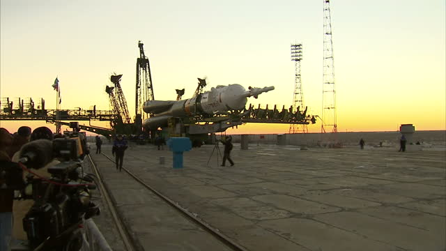 Exterior shots of the Soyuz rocket being moved onto launch pad and engineers standing around at Baikonur on December 13 2015 in Zhezkazgan Kazakhstan