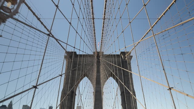 Exterior shots of the structure of the Brooklyn Bridge showing part of one of the large suspension cables and the weblike cabling surrounding the...