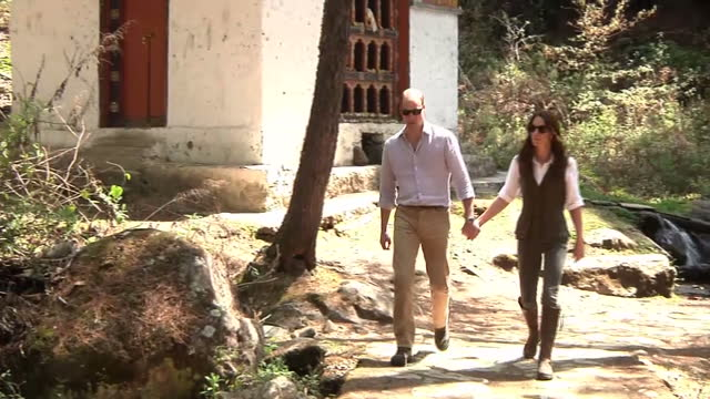 Exterior shots of the Taktsang Monastery set into the mountainside followed by the Duke and Duchess of Cambridge strolling up the mountain with local...