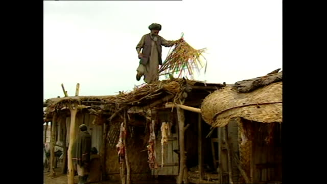 exterior shots of the town of khuj a bahuddin in afghanistan after a rainstorm with a man repairing a roof and vehicles and people in deep muddy... - asian tribal culture stock videos and b-roll footage