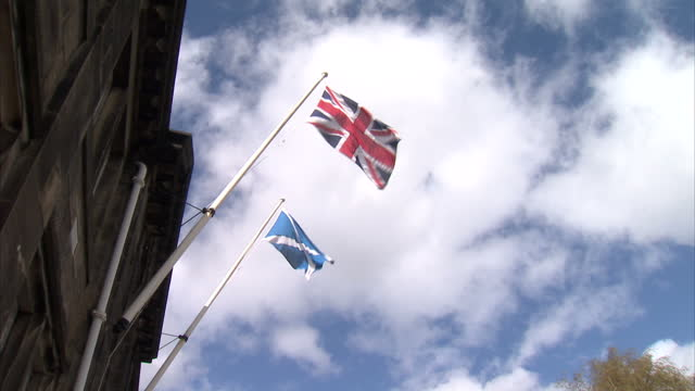 Exterior shots of the Union Jack flag the Saltire flag together outside an office building Scotland May Not Keep the British Pound If It Gains...