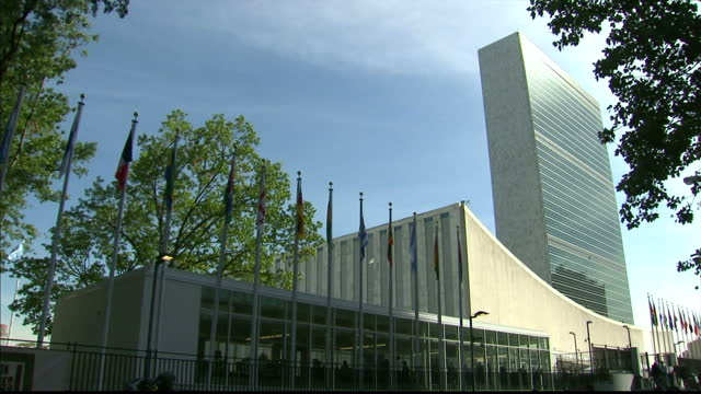 exterior shots of the united nations headquarters in new york show flags of the member nations blowing in wind and building on september 23 2014 in... - 本部点の映像素材/bロール
