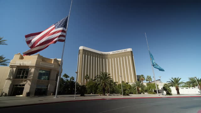 Exterior shots of the US flag and the state flag of Nevada flying at half mast in front of the Mandalay Bay Casino and Hotel in tribute to the...
