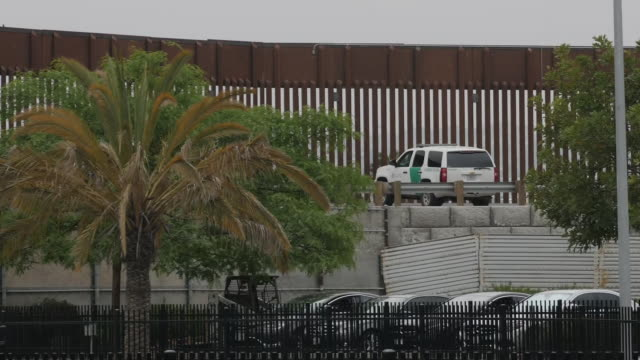 exterior shots of the us mexico border at san ysidro with border fence and pedestrian bridge with 'to mexico' signs, and cars passing along lanes... - 国境の壁点の映像素材/bロール