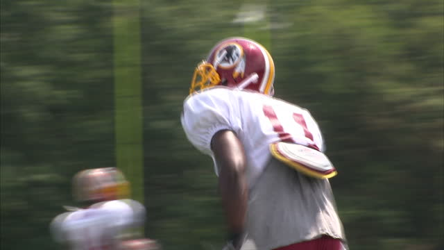 exterior shots of the washington redskins american football team warming up and training on pitch watched by onlookers, stretching and passing balls... - nfc east stock videos & royalty-free footage
