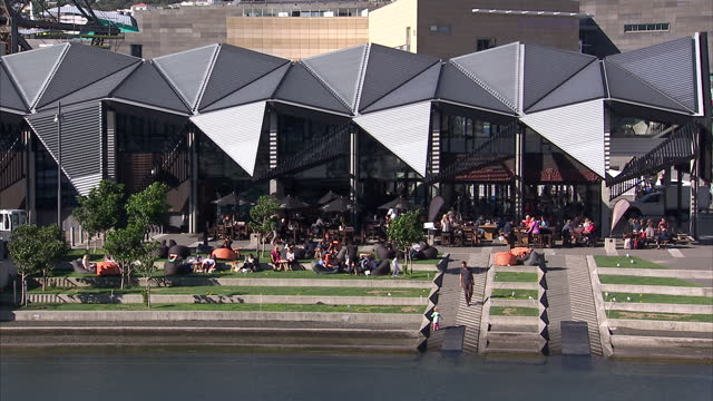 stockvideo's en b-roll-footage met exterior shots of the wharewaka function centre on the waterfront in wellington with people outside enjoying the sunshine and a pedalo boat on the... - waterfiets