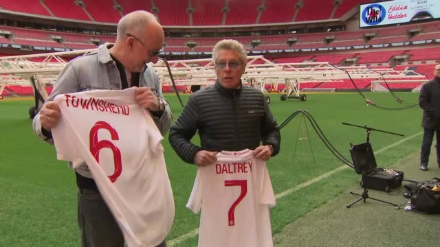Exterior shots of The Who's Pete Townshend and Roger Daltrey on the pitch of Wembley Stadium posing for photos with footballerstyle Tshirts bearing...