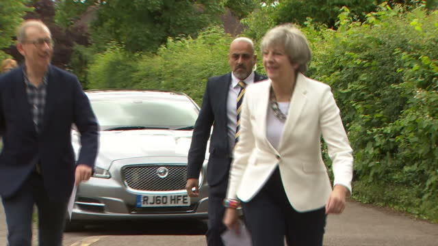 vídeos de stock, filmes e b-roll de exterior shots of theresa may arriving at her local polling station accompanied by her husband philip may including shots of a protester dressed as... - marido