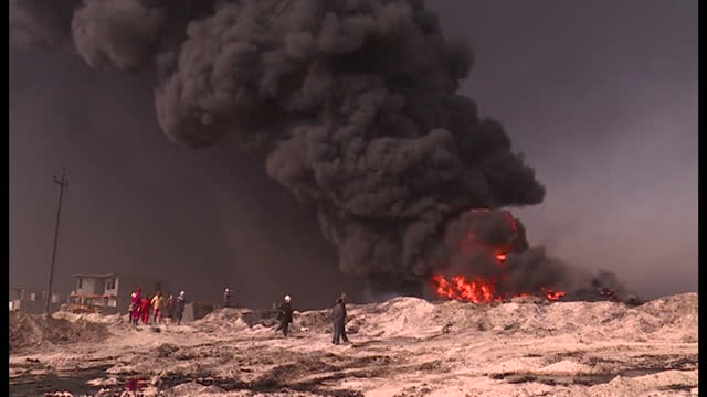 exterior shots of thick heavy smoke rising from oil wells and trucks moving dirt around after islamic state militants fleeing the region set oil... - irak stock-videos und b-roll-filmmaterial