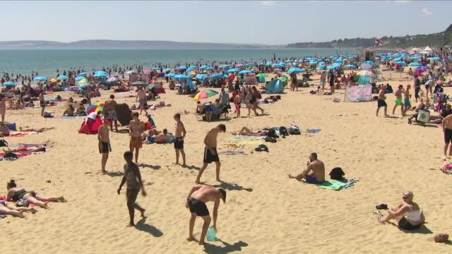 vídeos de stock, filmes e b-roll de exterior shots of thousands of people enjoying heatwave sunbathing and swimming on bournemouth beach on august 03 2018 in bournemouth england - onda de calor fenômeno natural