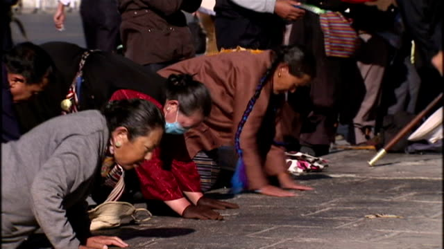 exterior shots of tibetan pilgrims bowing and kneeling in prayer in front of the potala palace lhasa the former residence of the dalai lama on june... - traditionally tibetan stock videos & royalty-free footage