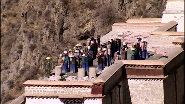 exterior shots of tibetan pilgrims on the rooftops of the potala palace in lhasa the former residence of the dalai lama on june 20 2009 in lhasa china - traditionally tibetan stock videos & royalty-free footage