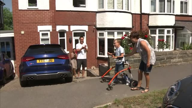 vídeos y material grabado en eventos de stock de exterior shots of tobias weller 9yearold boy with cerebral palsy completing his marathon walk in aid of charity cheered on by neighbours on 31 may... - telencéfalo