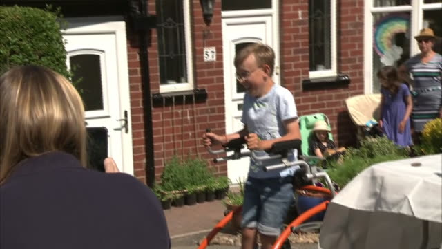 vídeos y material grabado en eventos de stock de exterior shots of tobias weller 9yearold boy with cerebral palsy preparing to complete his marathon walk in aid of charity cheered on by neighbours... - telencéfalo