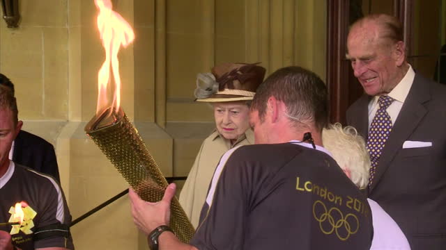 exterior shots of torchbearer gina macgregor running through rain with the the olympic torch and the queen prince philip looking at the olympic flame... - olympic torch stock videos & royalty-free footage