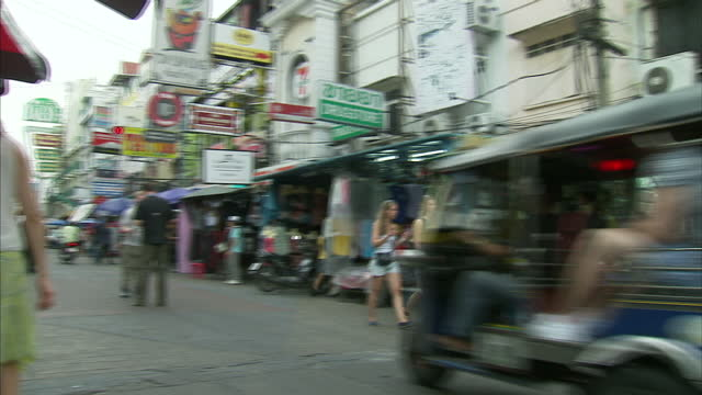 vidéos et rushes de exterior shots of tourist backpacker businesses including a massage parlour and budget hotel on khao san road and tourists walking around browsing... - massage room