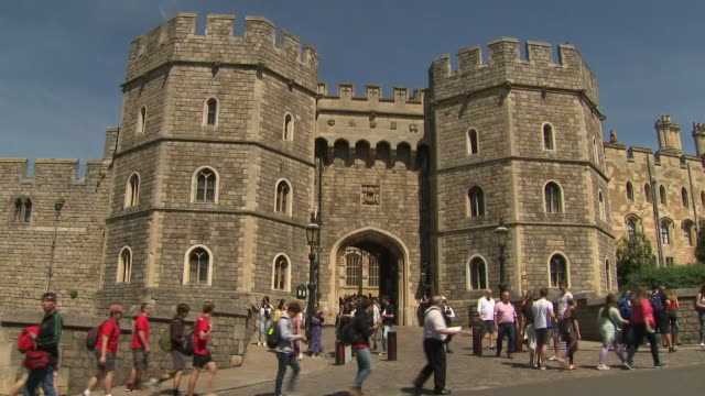 exterior shots of tourists and local people walking past windsor castle on a sunny day on 4 july 2019 in windsor, united kingdom - ウィンザー城点の映像素材/bロール