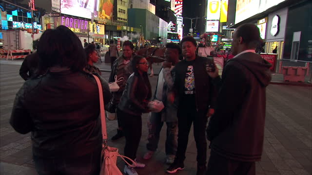 exterior shots of tourists at night time at times square milling around and taking selfies with road signs for broadway and various illuminated... - 2016 stock-videos und b-roll-filmmaterial