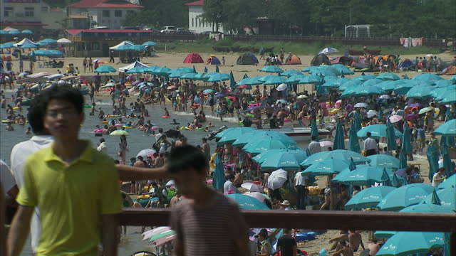 exterior shots of tourists enjoying the sunshine from a pagoda overlooking beidaihe beach which is packed with sunbathers and people paddling in the... - 見渡す点の映像素材/bロール