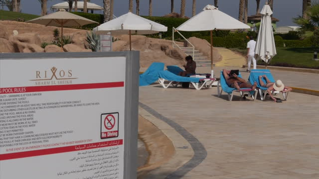 exterior shots of tourists lounging by the pool area and walking through the rixos hotel grounds in sharm el sheikh on november 08 2015 in sharm el... - adagiarsi video stock e b–roll
