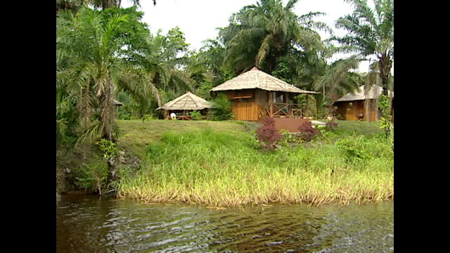 vídeos y material grabado en eventos de stock de exterior shots of tourists milling around next to raised huts on an ecotourism resort in rural gabon on december 16 2003 in libreville gabon - eco tourism