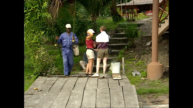Exterior shots of tourists milling around next to raised huts on an ecotourism resort in rural Gabon on December 16 2003 in Libreville Gabon