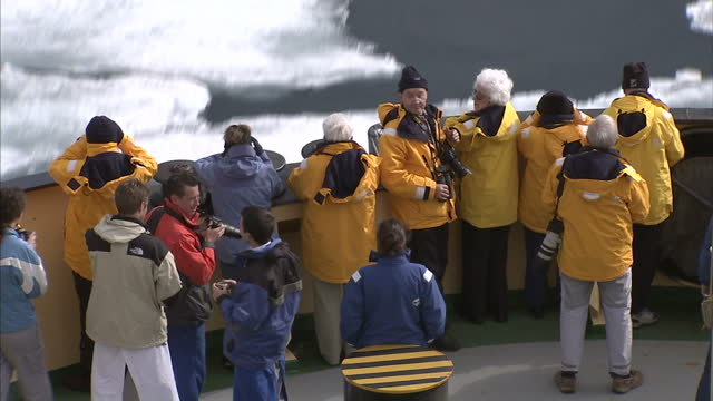 exterior shots of tourists on an expedition through the north west passage looking out at ice floes taking pictures on the bow of an icebreaker on... - northwest passage stock videos and b-roll footage