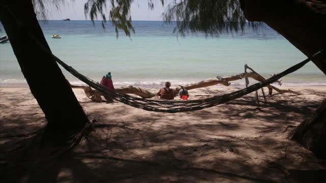 Exterior shots of tourists on Koh Tao beach sunbathing as a TV cameraman films in the wake of the murders of British backpackers Hannah Witheridge...